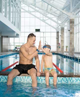 ハイタッチをする水泳コーチと水泳少年