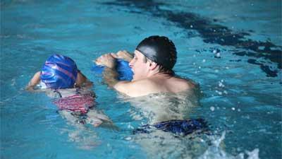 実際に泳いでお手本を見せているコーチ